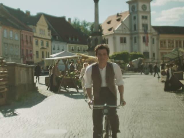 Velofahrer fährt durch eine Stadt.