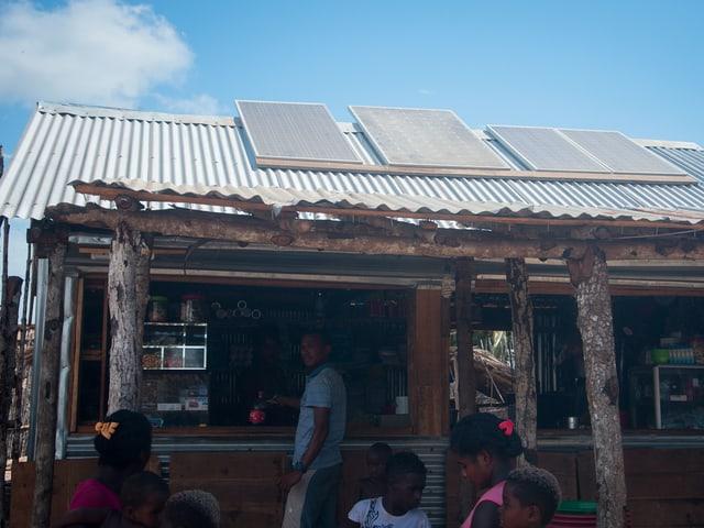 Eine Hütte mit Wellblechdach und Solarzellen.