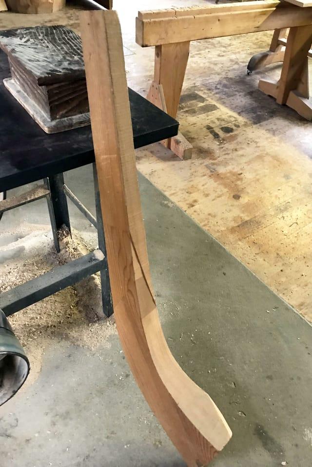 Ein Stück Holz, das die Form eines Alphorns andeutet.