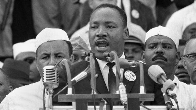 Martin Luther King hält seine Rede vor mehreren Mikrofonen.