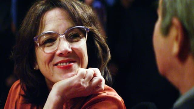 Bild aus dem Film: Dunkelhaarige Frau mit Brille im Gespräch mit einem Mann.