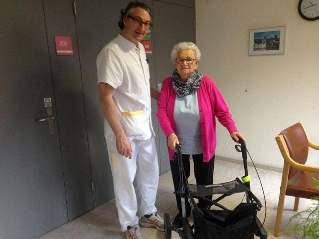 Pfleger in weissem Kittel mit einer Heimbewohnerin am Rolator.