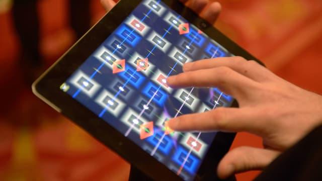 Eine Hand drückt auf dem Screen eines Tablets herum.