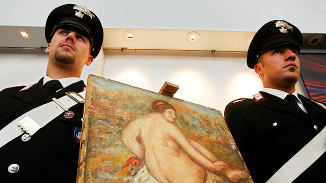 Zwei Polizisten stehen neben einem Gemälde.