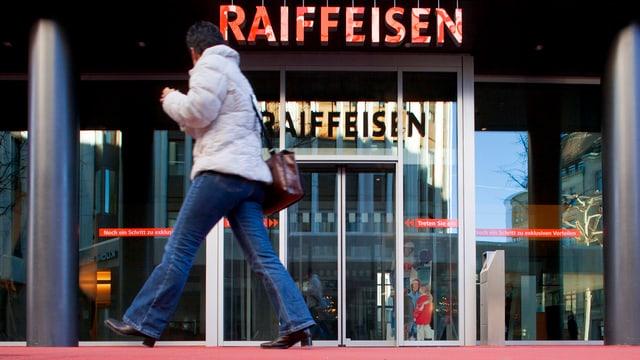 Eine Frau marschiert vor der Raiffeisen in St. Gallen durch.