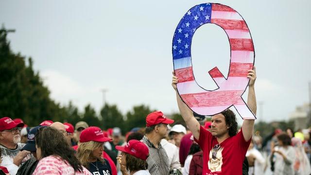 Mann hält an Wahlkampfveranstaltung ein Q aus Karton in die Luft