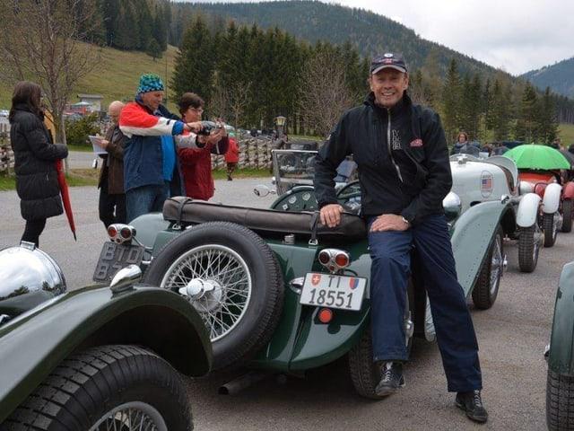 Peter Kraus lehnt sich während einer Oldtimer-Rallie lässig auf eines seiner Fahrzeuge.