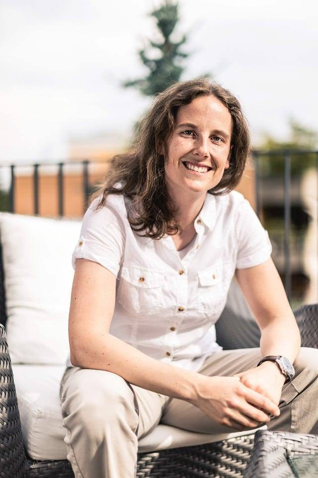 Ein Frau sitzt auf dem Balkon.