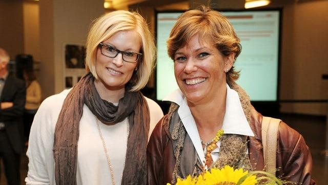 Zwei Frauen mit einem Blumenstrauss in der Hand lächeln in die Kamera.