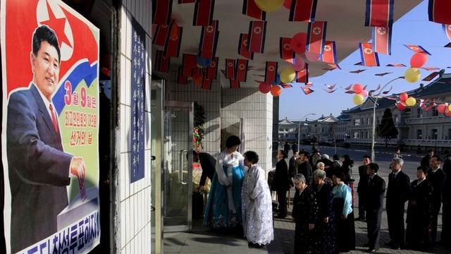 Schlange vor einem Wahllokal in Nordkorea. Kleine Fahnen schmücken die Decke der Überdachung, links ist ein Wahlplakat zu sehen