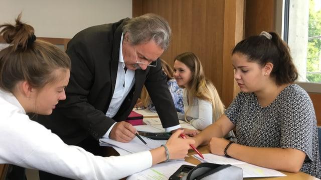 Ein Lehrer kontrolliert die Aufgaben von zwei Schülerinnen.