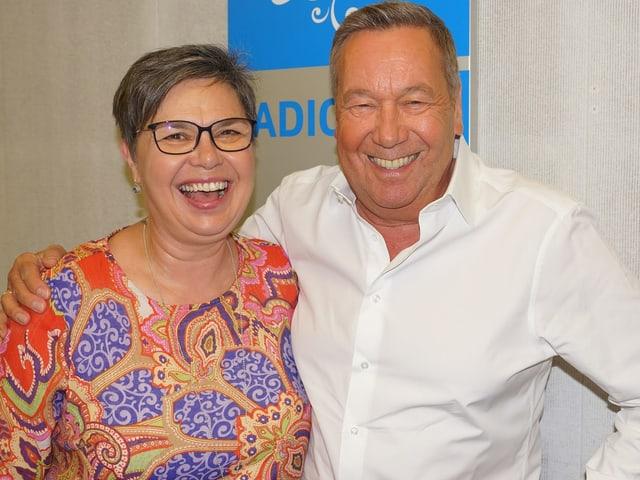 Eine Frau und ein Mann, die fröhlich in die Kamera lachen.
