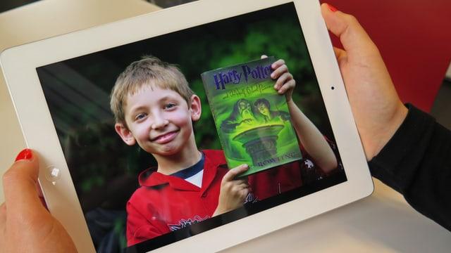 Screenshot: Junge mit Harry Potter Band in der Hand auf einem ipad