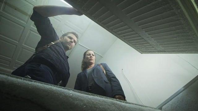 Blick aus einer Tiefkühltruhe auf einen Mann und eine Frau, die hineinschauen.