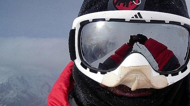 Ein Selfie mit einer Skibrille. Im Visier spiegelt sich die umliegende Bergwelt und die Sonne.