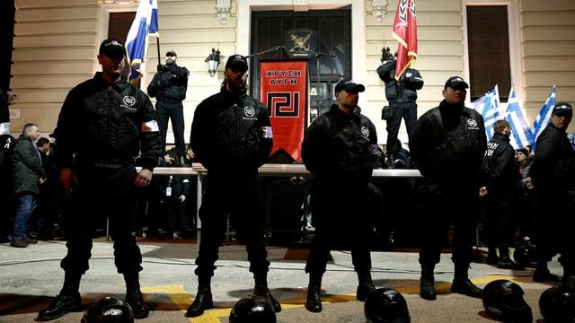 Schwarz gekleidete Männer in Springerstiefeln stehen vor griechischer und an ein Hakenkreuz erinnernden Fahne stramm.