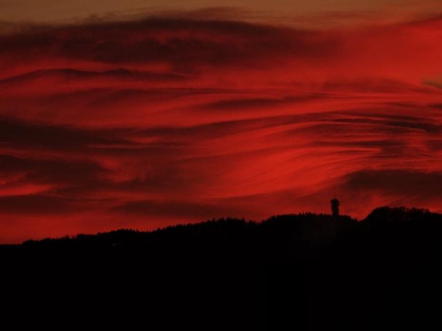 Flammenroter Himmel mit Wolken. Unten Konturen einer Hügelkette mit Turm.