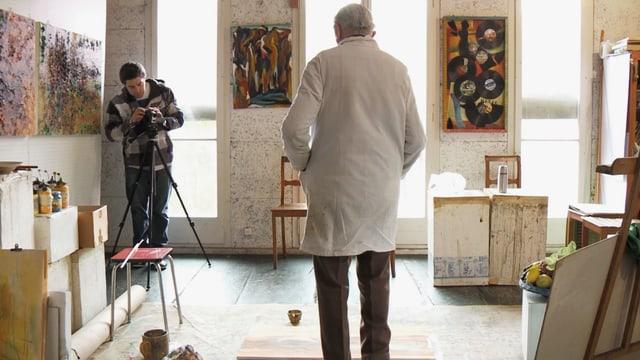 alter Mann steht jungem Mann vor Kamera Pose