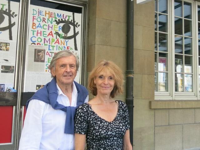 Ein Mann und eine Frau stehen vor Theaterplakaten