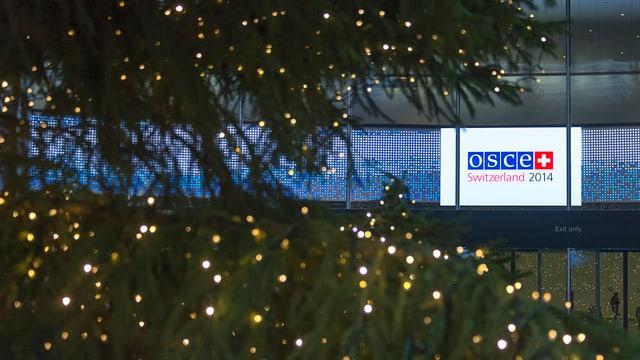 Ein Schild leuchtet hinter einem geschmückten Tannenbaum hervor: OSCE Switzerland 2014.