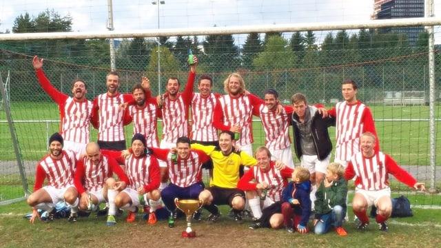 Das Team mit rot-weiss längsgestreiften Shirts posiert mit dem Cup vor dem Goal.