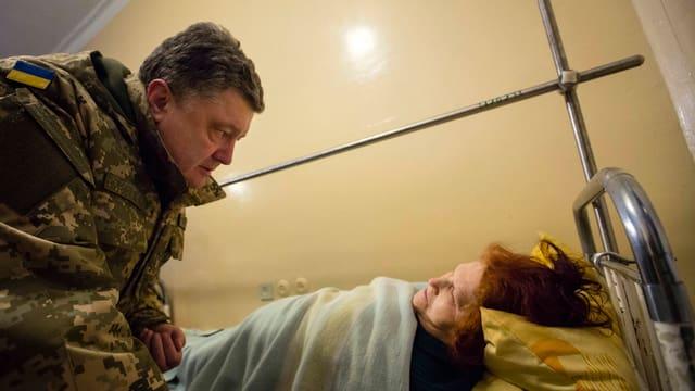 Ein Mann in Militärkleidung beugt sich über eine Frau auf einem Krankenbett.