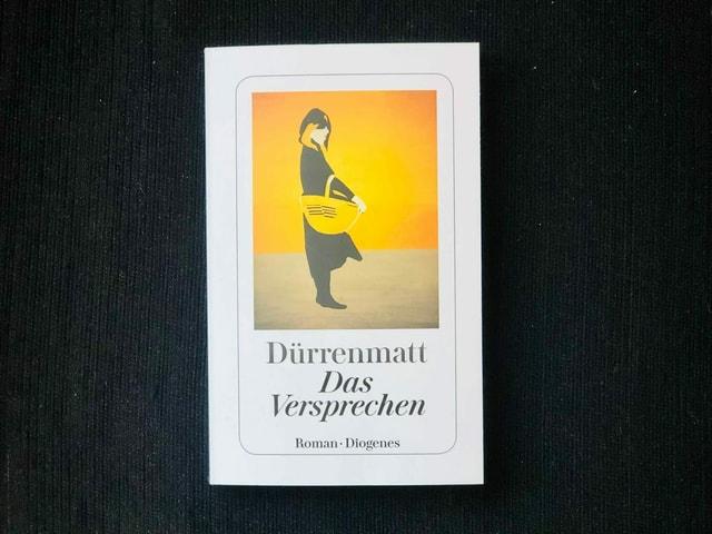 «Das Versprechen. Requiem auf den Kriminalroman» von Friedrich Dürrenmatt liegt auf einem dunklen Sessel