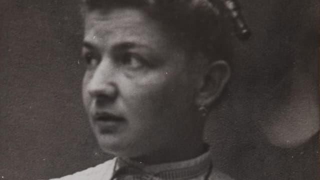 Alte Porträt-Fotografie in schwarz und weiss einer jungen Frau mit zusammengebundenen schwarz gelockten Haaren..