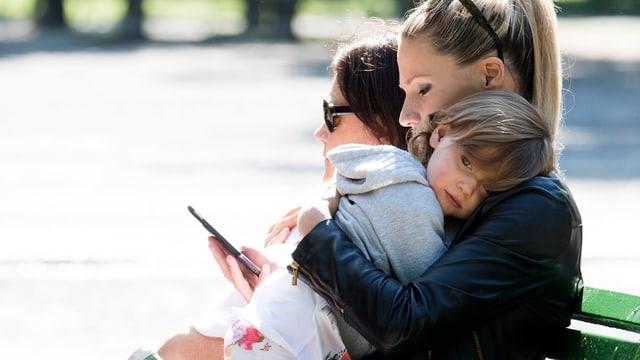 Michelle Hunziker sitzt auf einer Parkbank und hält ein Mädchen auf dem Arm.