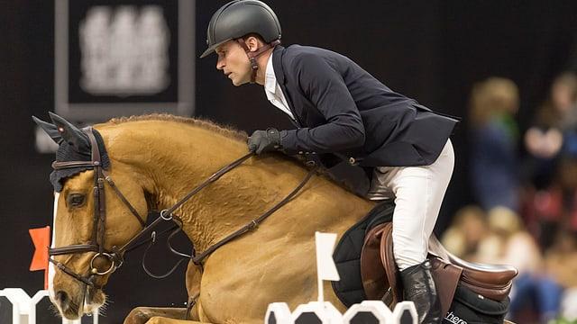 Romain Duguet bei einem Sprung im Sattel seines Pferdes.