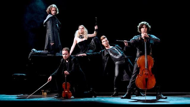 Eine Frau mit Flöte in der Mitte, um sie herum schwarzgekleidet und düster blickend 4 weitere Musiker.