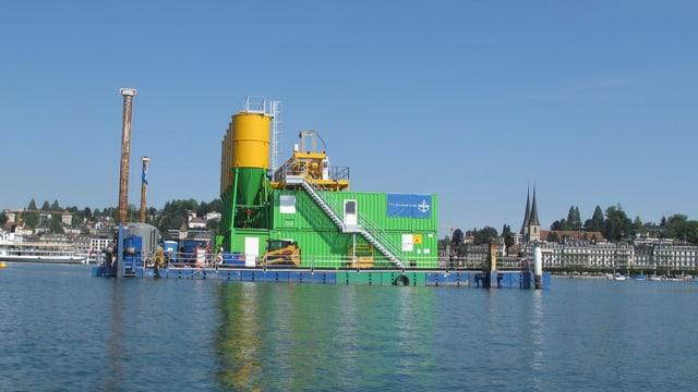 Ein gelbes Metallsilo steht auf einem Ponton im See. Dahinter die Silhoutte von Luzern.