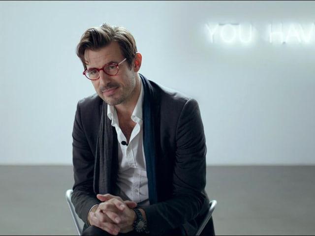 Ein Mann mit chnauz und Brille sitzt in einem leeren Raum.