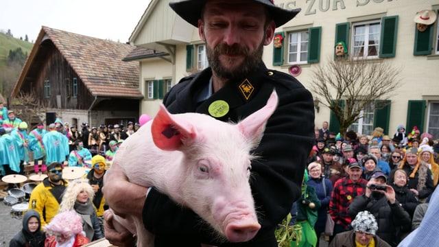 Ein Mann mit einem Schwein auf den Armen.