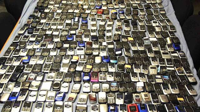 Blick auf einen Tisch mit unzähligen beschlagnahmten Handys.
