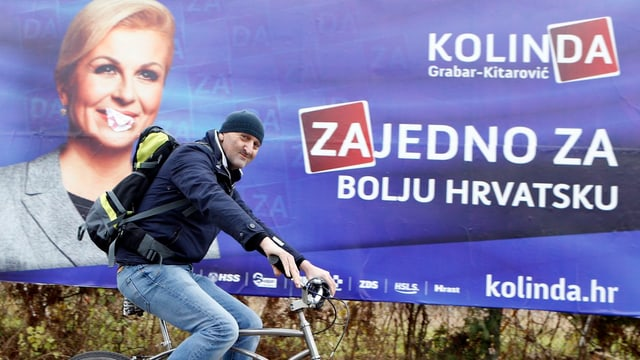 Mann fährt auf Velo vor Wahlplakat der Herausfordererin Kolinda Grabar Kitarovic vorbei.