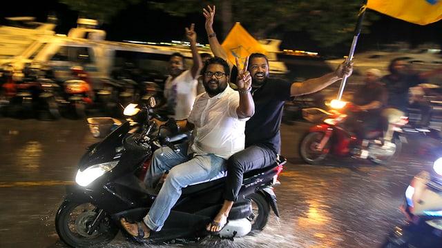 Jubelnde Männer mit Fahnen auf Motorrädern