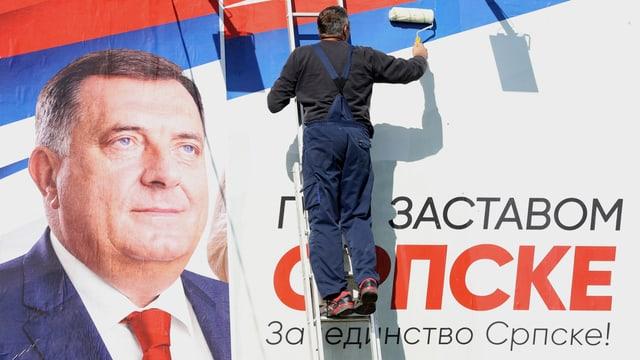 Mann befestigt Wahlplakat von Milorad Dodik