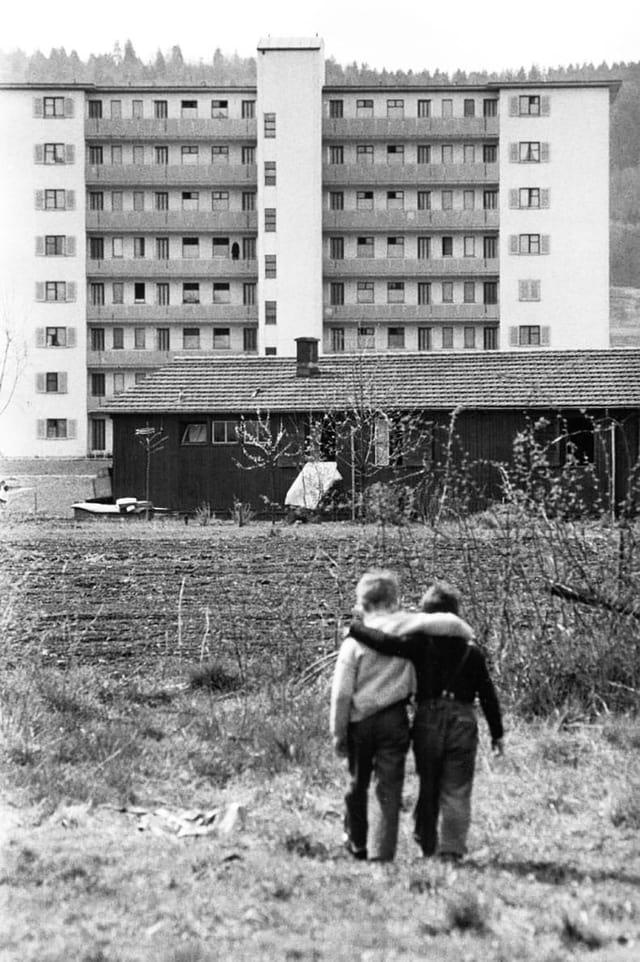 Zwei Buben umarmen sich vor einem Wohnblock. Sie laufen.