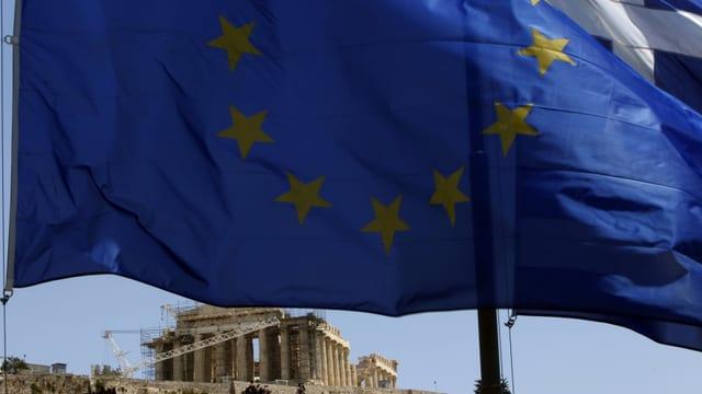 gronda bandiera blaua cun stailas melnas, davart sut in tempel grec che vegn renovà