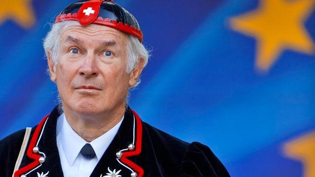 Ein Mann in typischer Schweizer Volkstracht vor der EU-Flagge.