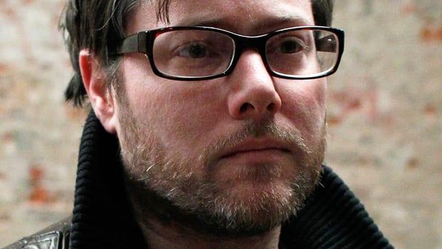 Porträt vom bärtigen Milo Rau in schwarzer Lederjacke und mit dunkler Hornbrille.