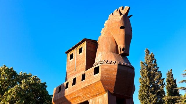 Ein überdimensional grosses Pferd aus Holz steht vor blauem Himmel. Im Pferdekörper sind Fenster zu sehen.