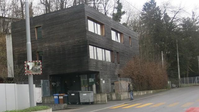 Ein dunkles Holzgebäude.