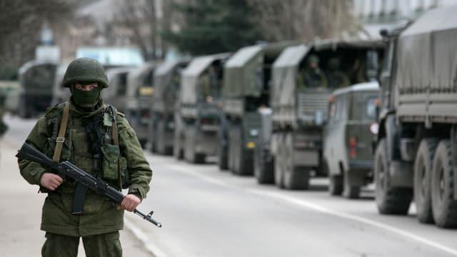 Soldat beobachtet einen Konvio von Militärfahrzeugen.