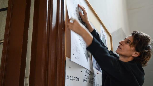 Eine Frau hängt gerade ein Plakat an eine Pinnwand.