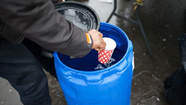 Eine Hand schöpft Wasser mit einem Becher aus einem blauen Kanister.