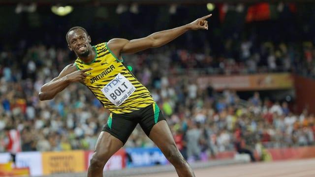 Der Athlete Usain Bolt feiert seinen Sieg mit Posen für die Kameras.
