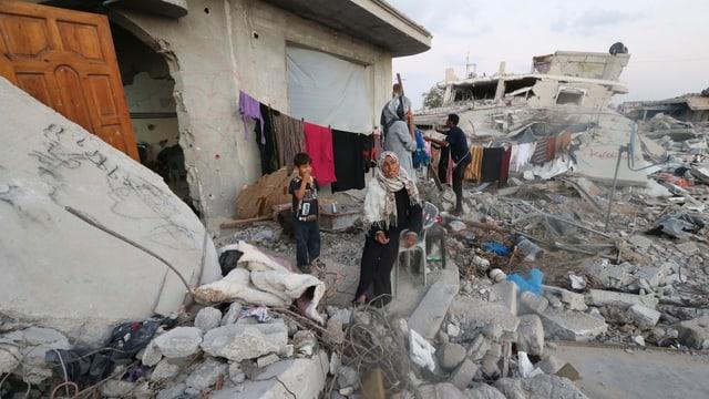 Frau und Kinder, umgeben von Trümmern ihres Hauses.