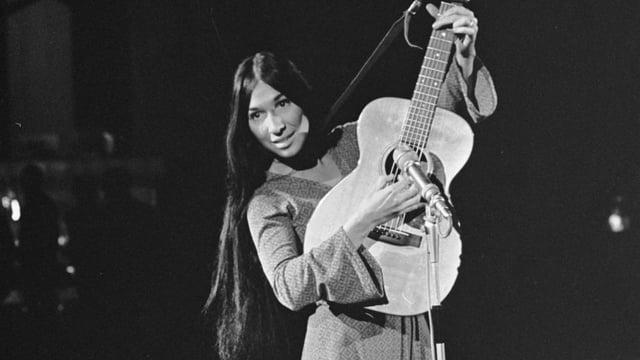Buffy Sainte-Marie mit einer Gitarre.
